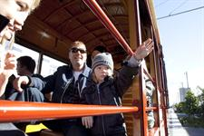 Passengers wave as the tram goes by